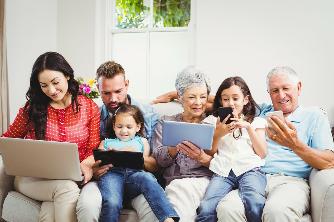 happy family using technologies while sitting on sofa